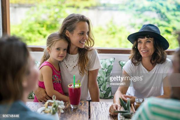 Woman with girl on her lap smiling at her friend in cafe
