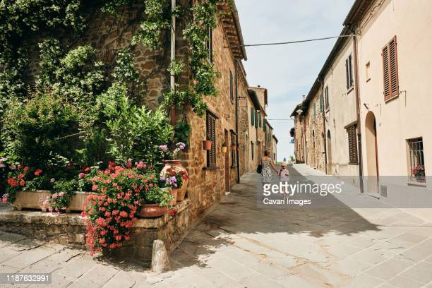 woman with girl walking along old houses with flowers - モンタルチーノ ストックフォトと画像
