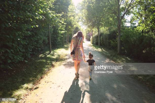 Woman with girl walking in park
