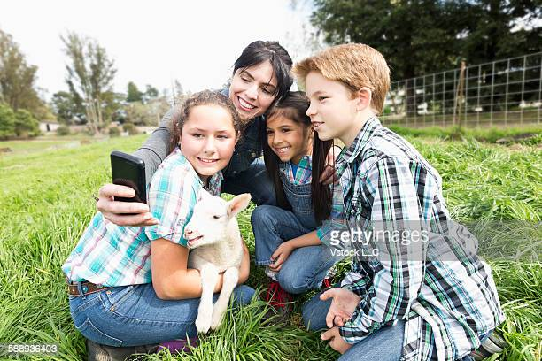 Woman with girls(6-7, 12-13) and boy (10-11) photographing with lamb