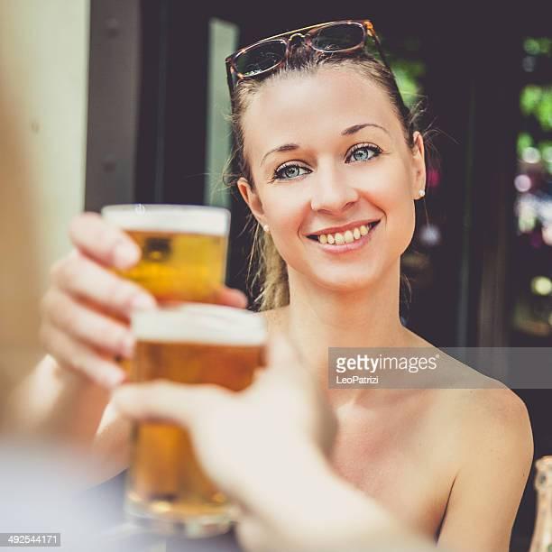 女性、ガラスの外のビールパブ