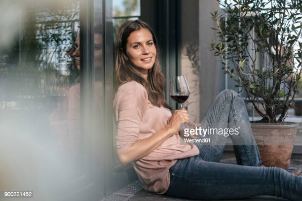 woman with glass of red wine relaxing on balcony - alcool photos et images de collection