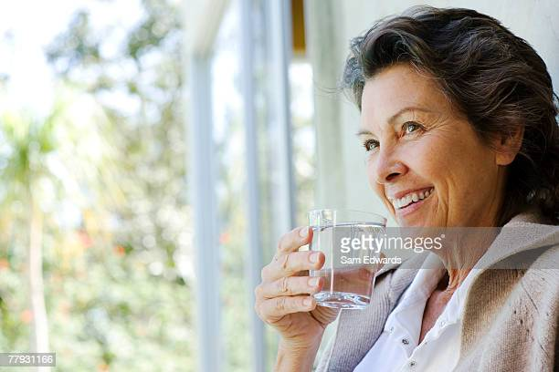 woman with glass of water standing in doorway - drinking water stock pictures, royalty-free photos & images