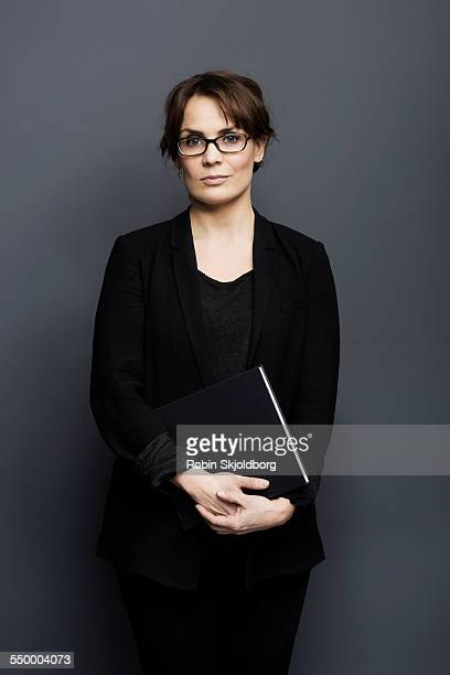 Woman with glasses holding black book