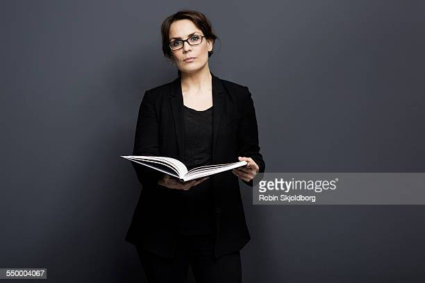 woman with glasses holding book - solo una donna di età media foto e immagini stock