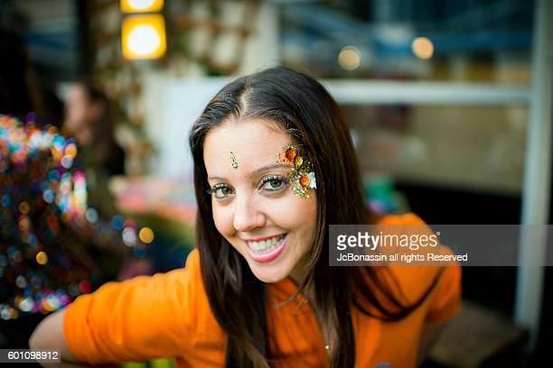 woman with glitter on her face smiling - jcbonassin stock pictures, royalty-free photos & images