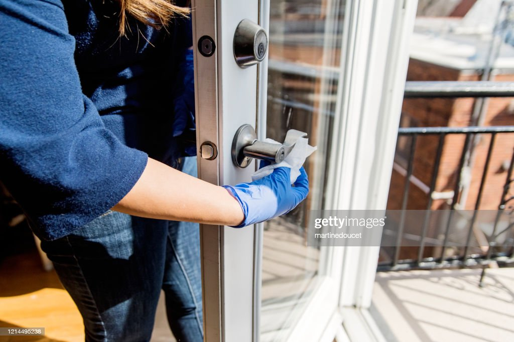 Woman with glove wiping door handle. : Stock Photo