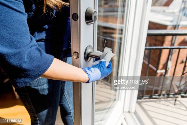 """woman with glove wiping door handle. - """"martine doucet"""" or martinedoucet stock pictures, royalty-free photos & images"""