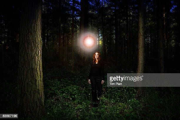 Woman with glowing ball of light in forest.