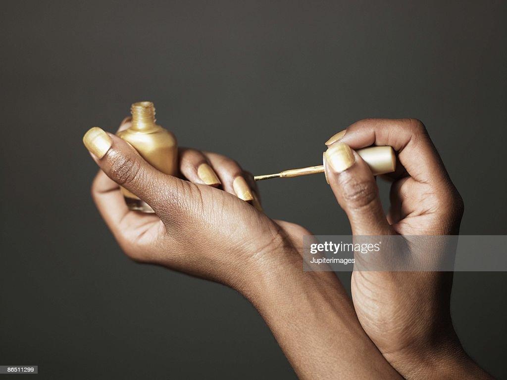 Woman with gold nail polish : Stock Photo
