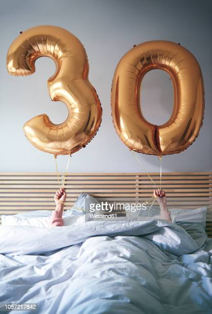 Woman with golden balloons celebrating her birthday in bed