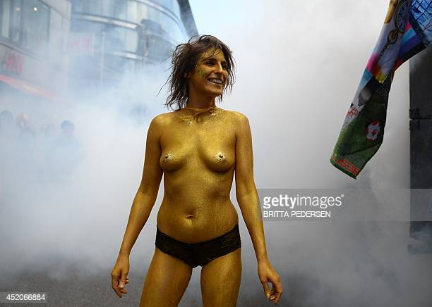 A woman with golden body paint takes part in a parade to demonstrate for ethical social and environmental standards within the fashion industry in...