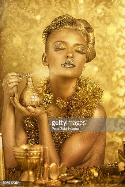 woman with golden body painting applying perfume