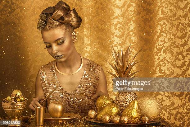 woman with golden body painting having golden dinner