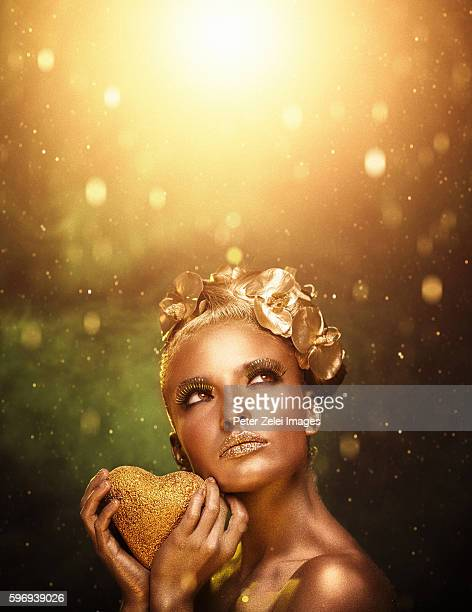 woman with golden body painting holding a golden heart