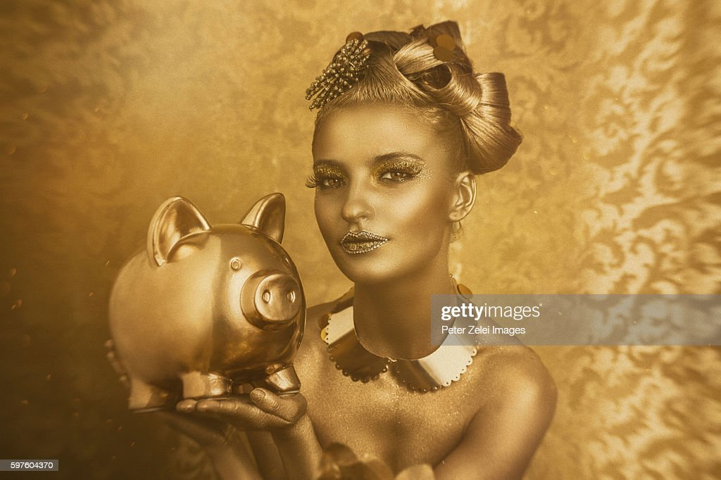 woman with golden body painting holding a golden piggy bank : Stock Photo