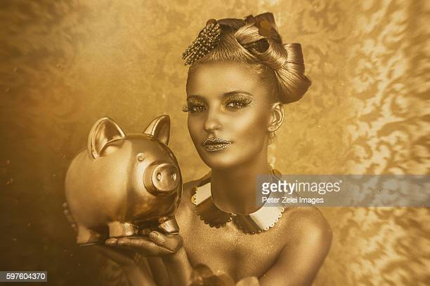 woman with golden body painting holding a golden piggy bank