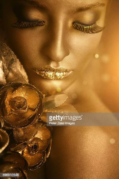 woman with golden body painting holding golden roses