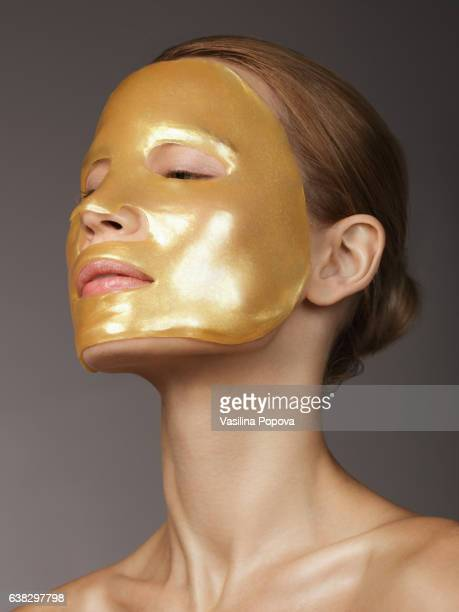 Woman with golden mask on her face