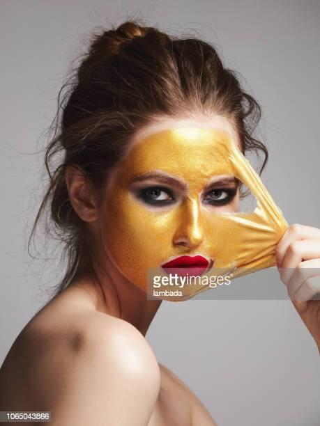 mulher com máscara peel-off dourada - preocupação com o corpo - fotografias e filmes do acervo