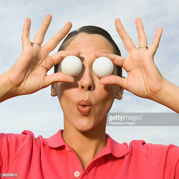 woman with golf balls over eyes - golf humour photos et images de collection