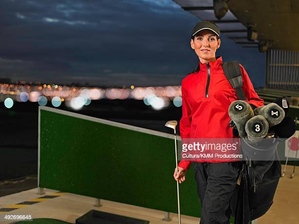 woman with golf clubs at driving range - driving range stock photos and pictures