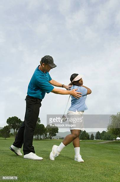 Woman with golf instructor