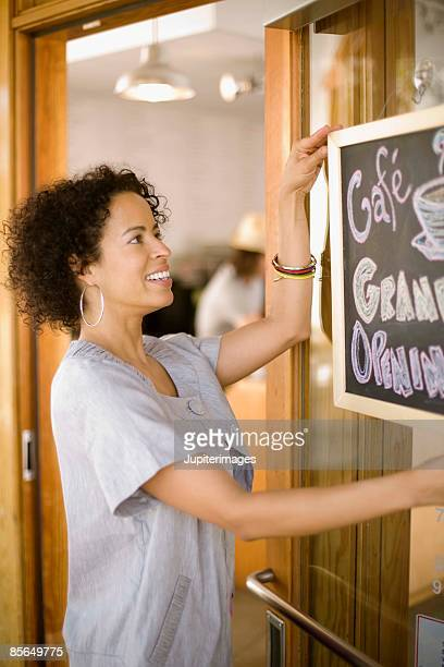 woman with grand opening sign for cafe - opening ceremony stock pictures, royalty-free photos & images