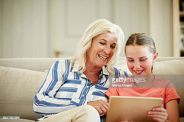 Woman with granddaughter using digital tablet