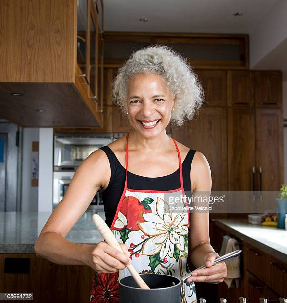 Woman with gray hair cooking in kitchen