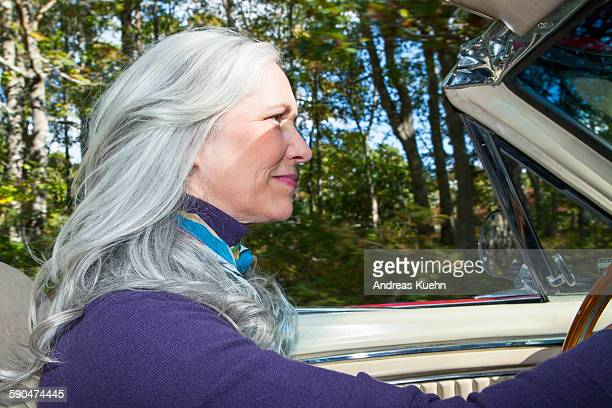 woman with gray hair driving in a convertible. - convertible stock pictures, royalty-free photos & images