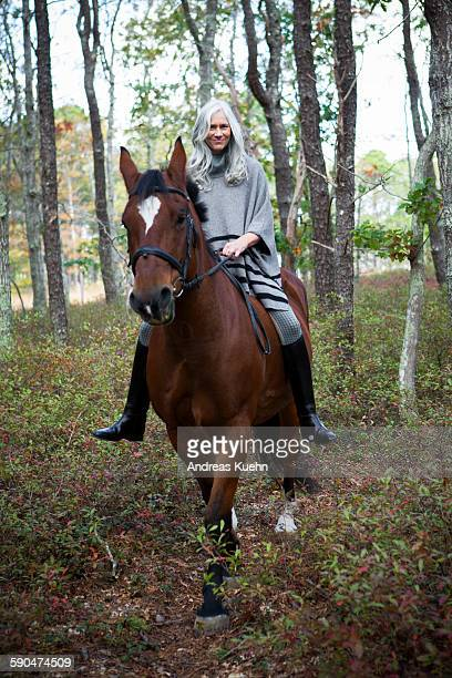 Woman with gray hair riding a horse in the woods.