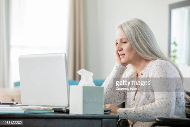 woman with gray hair talks with doctor on computer during telehealth appointment - telemedicine stock photos and pictures
