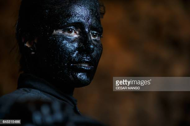 A woman with grease on her face to represent 'Diablos de Luzon' prepares during the carnival in Luzon near Guadalajara on February 25 2017 / AFP /...