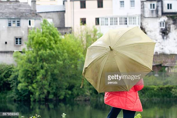 Woman with green umbrella, river and buildings.