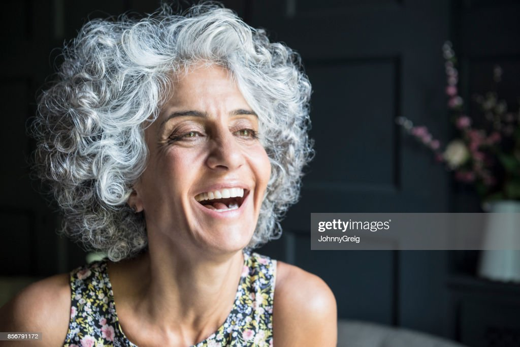 Woman with grey curly hair looking away and laughing : Stock Photo