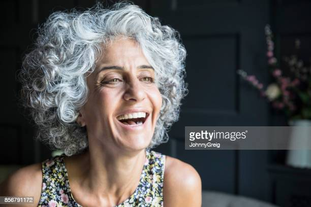 Woman with grey curly hair looking away and laughing
