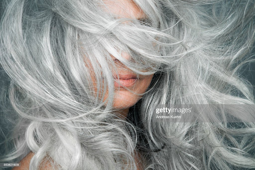 Woman with grey hair blowing across her face. : Stock-Foto