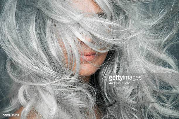 Woman with grey hair blowing across her face.