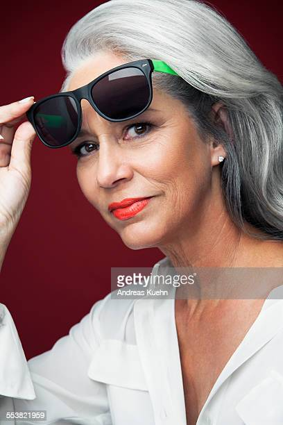 Woman with grey hair holding sunglasses.