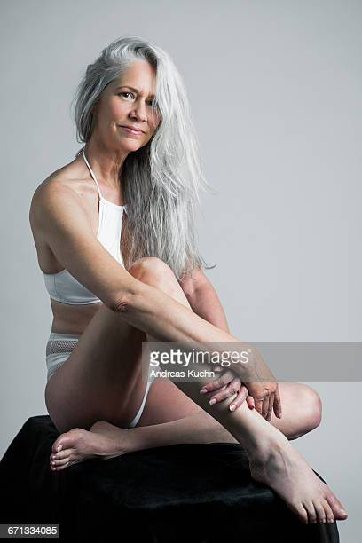 Woman with grey hair in a two piece swimsuit.