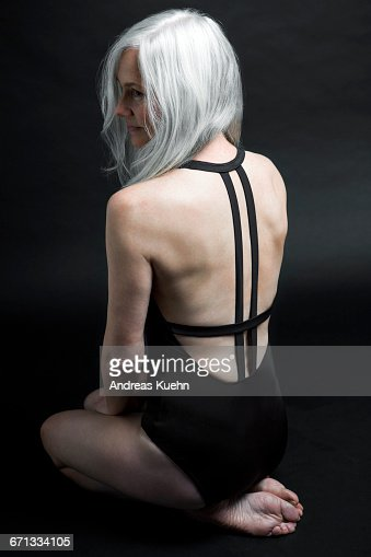 Woman With Grey Hair In Swimsuit Kneeling Down Stock Photo