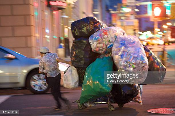 CONTENT] woman with grocery cart stacked high with bags of aluminum cans for recycling midtown Manhattan New York City