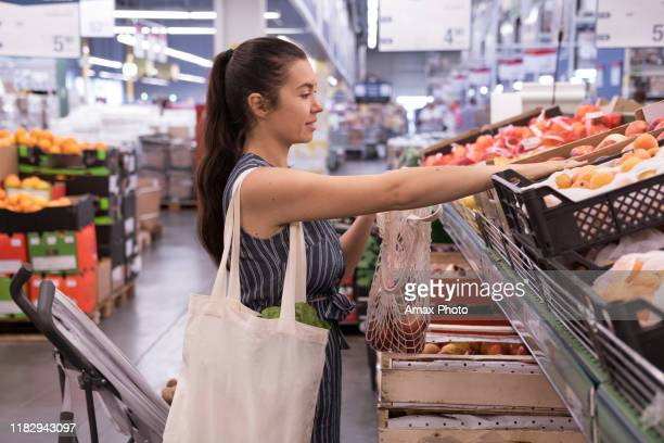 woman with grocery eco bag of vegetables in a supermarket background. - reusable bag stock pictures, royalty-free photos & images