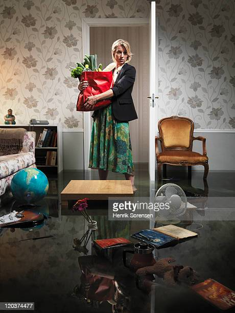 woman with grocery in flooded room