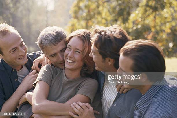 Woman with group of males, smiling
