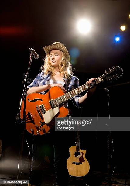 Woman with guitar on stage, portrait