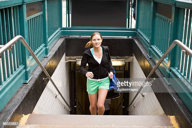 Woman with gym bag running up stairs from subway station