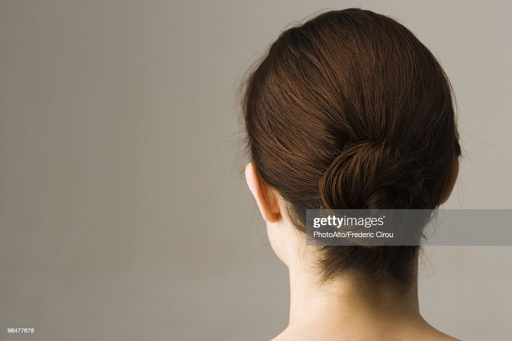 Woman with hair arranged in chignon, rear view : Stock Photo