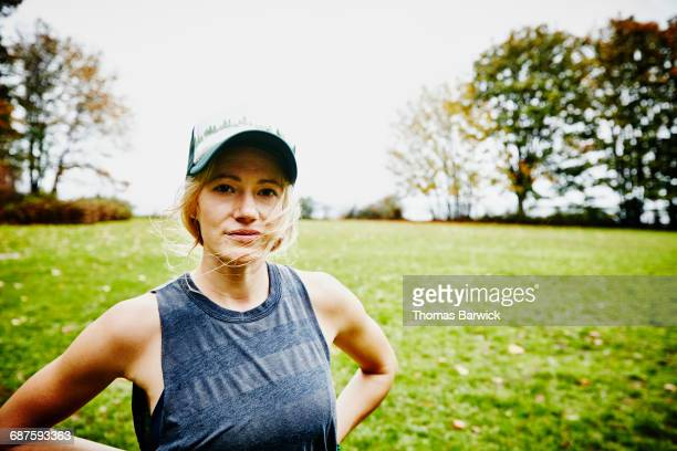 Woman with hair blowing in wind in park after run